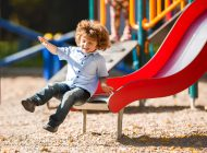 Happy little boy sliding and having fun outdoors at playground.